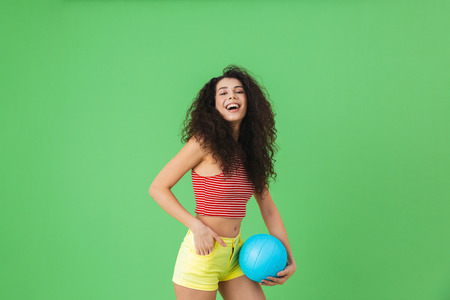 Image of young woman 20s wearing summer clothes smiling and holding volley ball while standing against green background