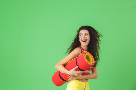 Photo of european woman 20s smiling and carrying yoga mat during workout against green wall