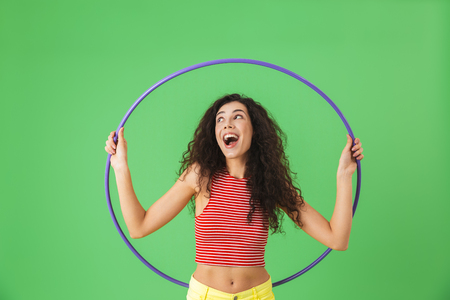 Photo of delighted woman 20s wearing summer clothes doing exercises with hula ring during gymnastics against green wall Reklamní fotografie