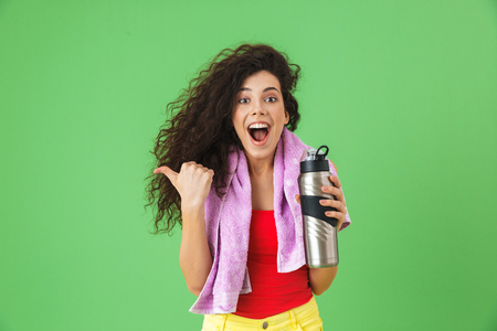 Image of delighted woman 20s in sportswear rejoicing and drinking water after training standing against green background