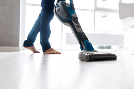Close up of a man vacuuming the floor at home 스톡 콘텐츠