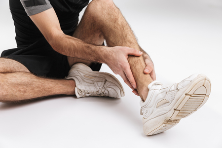 Croppe image of a young sports fitness man sitting on floor isolate over white wall background with painful feelings in leg.