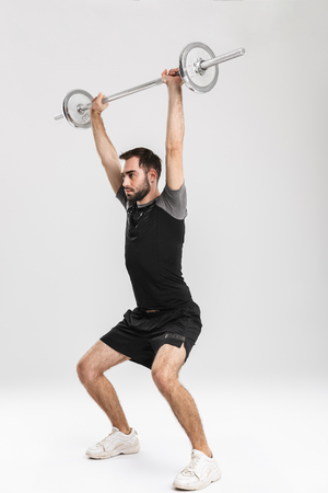 Image of a young sports fitness man isolate over white wall background make exercises with barbell. Banque d'images