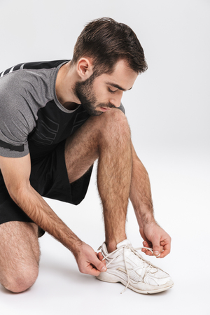 Image of a handsome young sports fitness man runner posing isolate over white wall background tie his laces. 写真素材