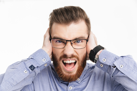 Close up image of Screaming bearded elegant man in eyeglasses covering his ears and lookin at the camera over grey background