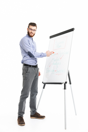 Full length image of Smiling bearded elegant man in eyeglasses making presentation while using flipchart and looking at the camera over grey background Reklamní fotografie