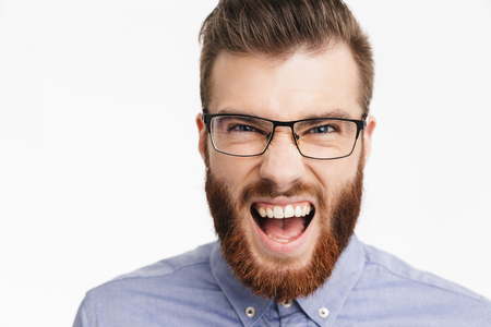 Close up view of Happy screaming bearded elegant man in eyeglasses rejoices and looking at the camera over grey background Stock Photo