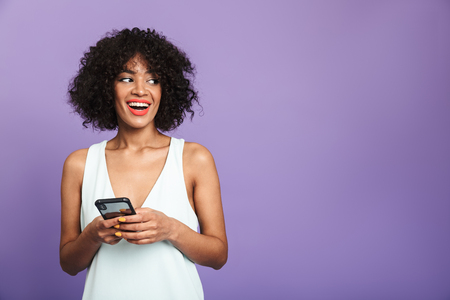 Happy pretty african woman holding smartphone and looking away over violet background