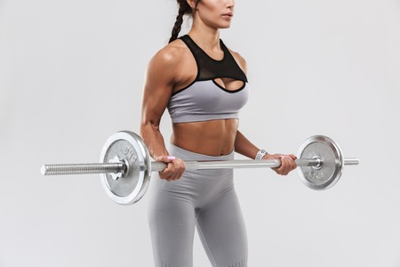 Cropped picture of a beautiful young amazing strong sports fitness woman posing isolated over white wall background make exercises with barbell.