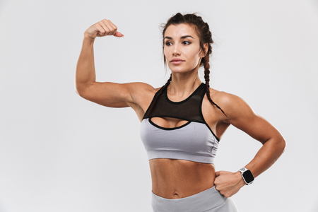 Image of a beautiful young amazing strong sports fitness woman posing isolated over white wall background showing biceps.