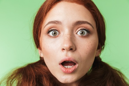 Image of a beautiful shocked young redhead girl posing isolated over green wall background.