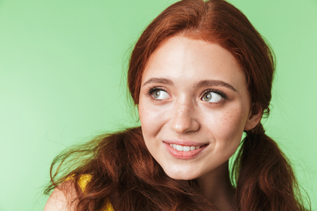 Image of a beautiful happy young redhead girl posing isolated over green wall background. Stock fotó