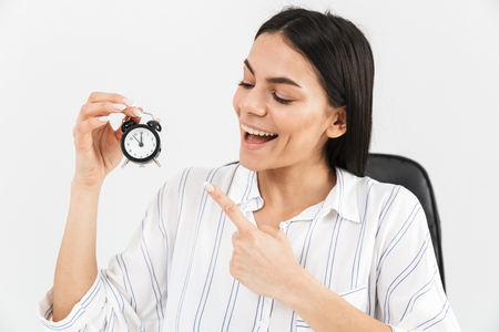 Photo of successful businesswoman 30s rejoicing while sitting in armchair in office and holding tiny alarm clock isolated over white background