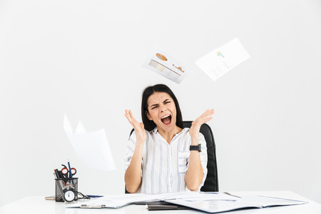 Photo of neurotic brunette businesswoman 30s screaming and stressing while working with paper documents in office isolated over white background