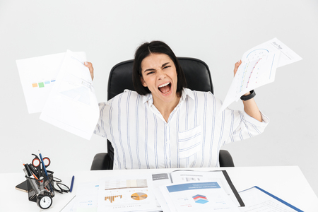 Photo of european brunette businesswoman 30s screaming and stressing while working with paper documents in office isolated over white background