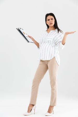 Full length photo of displeased pregnant businesswoman 30s holding clipboard and throwing up hands while standing isolated over white background Stock Photo