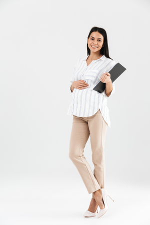 Full length photo of healthy pregnant businesswoman 30s holding clipboard and touching her big tummy while standing isolated over white background
