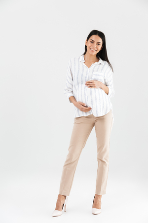 Full length photo of caucasian pregnant businesswoman 30s smiling and touching her big tummy while standing isolated over white background