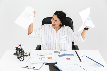 Photo of displeased brunette businesswoman 30s screaming and stressing while working with paper documents in office isolated over white background