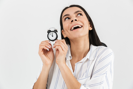 Photo of caucasian businesswoman 30s rejoicing while sitting in armchair in office and holding tiny alarm clock isolated over white background