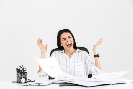 Photo of shocked brunette businesswoman 30s screaming and stressing while working with paper documents in office isolated over white background