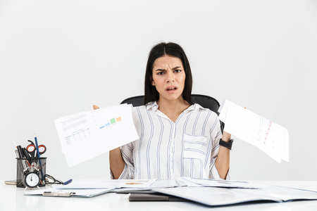 Photo of tense brunette businesswoman 30s screaming and stressing while working with paper documents in office isolated over white background Stock Photo