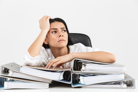 Photo of upset brunette businesswoman 30s working and sitting in office with bunch of paper folders on table isolated over white background
