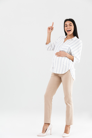 Full length photo of young pregnant businesswoman 30s smiling and touching her big tummy while standing isolated over white background