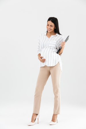 Full length photo of european pregnant businesswoman 30s holding clipboard and touching her big tummy while standing isolated over white background