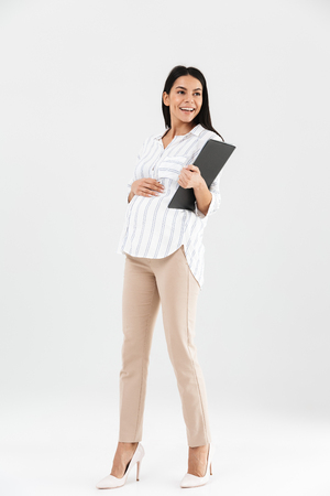 Full length photo of smiling pregnant businesswoman 30s holding clipboard and touching her big tummy while standing isolated over white background Stock Photo