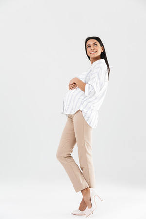 Full length photo of european pregnant businesswoman 30s smiling and touching her big tummy while standing isolated over white background Stock Photo