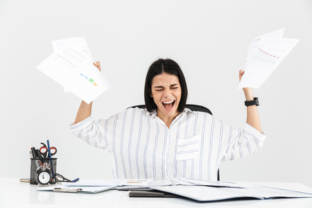 Photo of nervous brunette businesswoman 30s screaming and stressing while working with paper documents in office isolated over white background