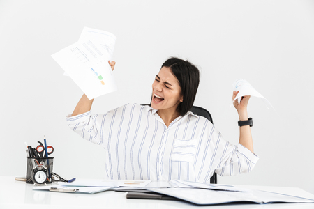 Photo of confused brunette businesswoman 30s screaming and stressing while working with paper documents in office isolated over white background Stock Photo