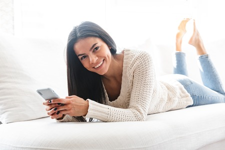 Lovely young woman relaxing on a couch at home, using mobile phone