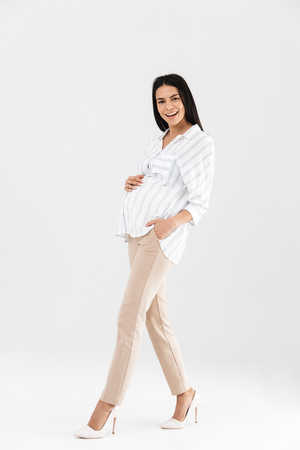 Full length photo of beautiful pregnant businesswoman 30s smiling and touching her big tummy while walking isolated over white background Stock Photo