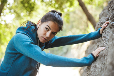 Close up of an attractive young fitness woman wearing sportswear exercising outdoors, resting after workout