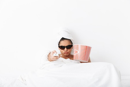 Image of a beautiful serious woman with towel on head lies in bed under blanket isolated over white wall background wearing sunglasses eat popcorn watch film tv.