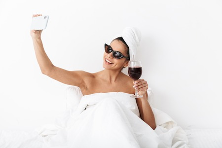 Image of a beautiful woman with towel on head lies in bed under blanket isolated over white wall background wearing sunglasses drinking wine take selfie by mobile phone. 版權商用圖片