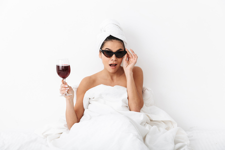 Image of a beautiful woman with towel on head lies in bed under blanket isolated over white wall background wearing sunglasses drinking wine.