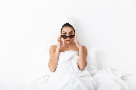 Image of a beautiful shocked woman with towel on head lies in bed under blanket isolated over white wall background wearing sunglasses.