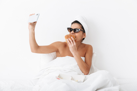 Image of a beautiful emotional woman with towel on head lies in bed under blanket isolated over white wall background wearing sunglasses eat burger take a selfie. 写真素材