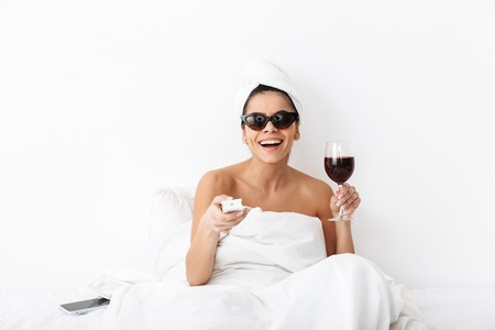 Image of a beautiful woman with towel on head lies in bed under blanket isolated over white wall background wearing sunglasses drinking wine watch tv film. Imagens