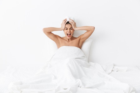 Image of a beautiful displeased screaming emotional amazing woman with towel on head lies in bed under blanket isolated over white wall background.
