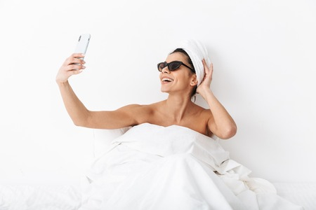 Image of a beautiful emotional woman with towel on head lies in bed under blanket isolated over white wall background wearing sunglasses take a selfie by mobile phone.