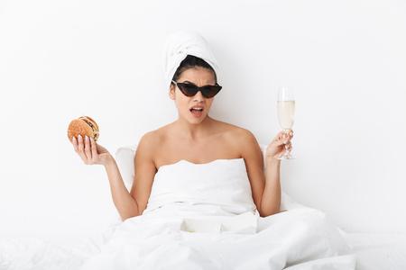 Imagen de una hermosa mujer emocional confundida con una toalla en la cabeza yace en la cama bajo una manta aislada sobre fondo de pared blanca con gafas de sol con hamburguesa y champán.