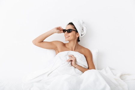 Image of a beautiful amazing woman with towel on head lies in bed under blanket isolated over white wall background wearing sunglasses.