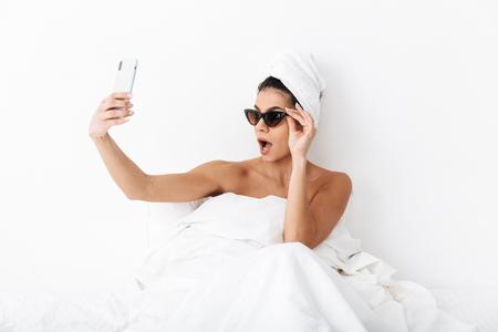 Das Bild einer schönen emotionalen Frau mit Handtuch auf dem Kopf liegt im Bett unter einer Decke, die über weißem Wandhintergrund isoliert ist und eine Sonnenbrille trägt, um ein Selfie mit dem Handy zu machen.