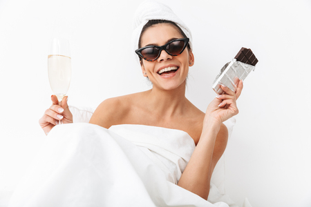 Image of a beautiful woman with towel on head lies in bed under blanket isolated over white wall background wearing sunglasses eat chocolate drinking champagne.