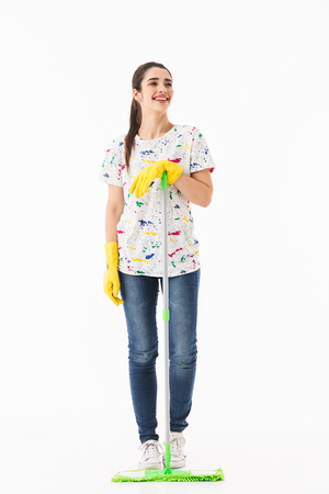 Full length photo of smiling housewife 20s wearing yellow rubber gloves for hands protection washing the floor with mop isolated over white background