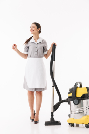 Full length photo of caucasian maid 20s dressed in uniform cleaning floor with vacuum during housework isolated over white background Stok Fotoğraf